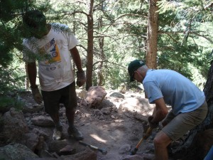 Gareth Martins (white tee shirt), Marketing Director for Osprey Packs and a volunteer (blue tee shirt) from IMBA, a Boulder based MTC trail advocacy team up to clean the trail together.